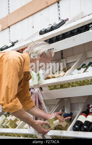 Customer reading label on a wine bottle in supermarket, Augsburg, Bavaria, Germany - Stock Photo