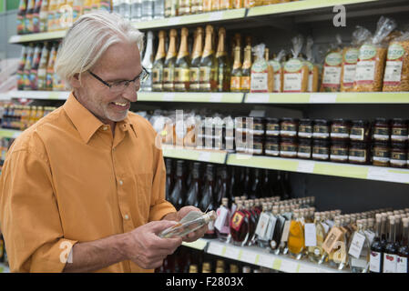 Customer reading label on a schnapps bottle in supermarket, Augsburg, Bavaria, Germany - Stock Photo
