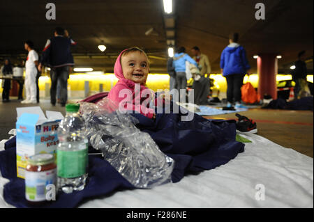 Salzburg, Germany. 13th Sep, 2015. A little girl from Syria sits on the ground in an underground car park which - Stock Photo