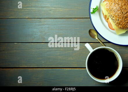Black coffee with wholegrain sandwich roll on a wooden backdrop - Stock Photo