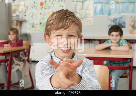 Schoolboy with a slingshot and smiling in classroom, Munich, Bavaria, Germany - Stock Photo