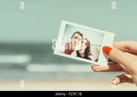 Girl Hand Holding Retro Instant Photo Of Young Happy Couple On The Beach - Stock Photo
