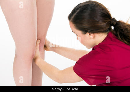 physiotherapist doing knee evaluation to a woman patient - Stock Photo