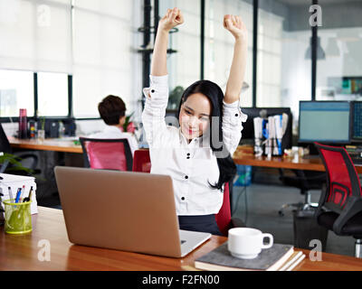 young asian business woman celebrating completion of task - Stock Photo