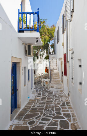 Street with traditional architecture and decorated cobble stone pavement in Naousa village on Paros island, Greece - Stock Photo