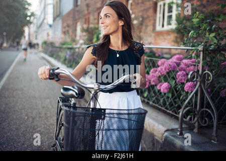 Cheerful young woman looking away while walking down the street with a bike. Female with a bicycle on city road - Stock Photo