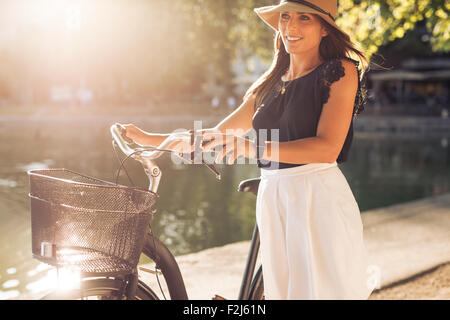 Outdoor shot of a pretty young woman with a bicycle in park during summer. Female with a cycle looking away smiling - Stock Photo