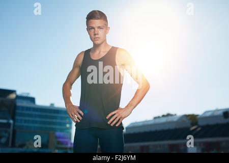 Outdoor shot of young man on stadium preparing for a run. Professional male athlete with his hands on hips looking - Stock Photo