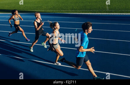 Group of multiracial athletes practicing running on racetrack. Male and female athletes during running session at - Stock Photo