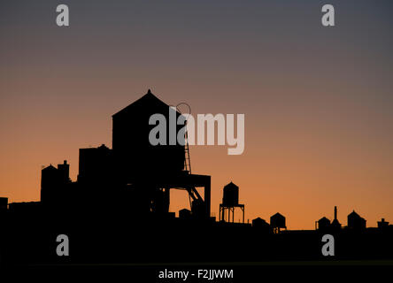A silhouetted view of water towers on Manhattan's Upper West Side at sunrise;  New York City, New York State, U.S.A. - Stock Photo