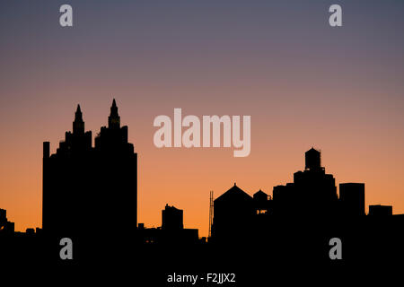 A silhouetted view of old buildings and water towers on Manhattan's Upper West Side at sunrise;  New York City. - Stock Photo