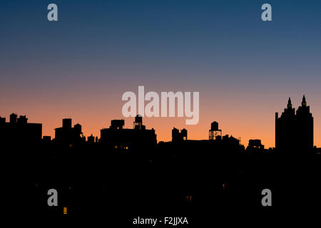 A silhouetted view of the Manhattan skyline and El Dorado building on the Upper West Side at sunrise;  New York - Stock Photo