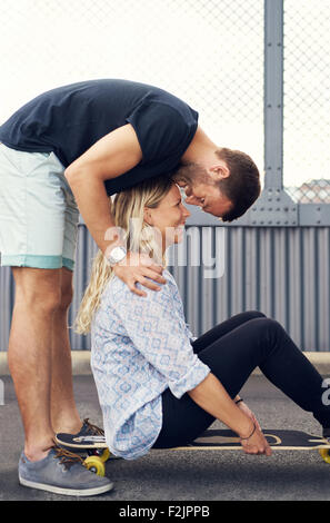Man leaning over woman kissing her while she smiles - Stock Photo
