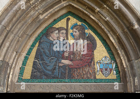 Jesus Christ blessing Benedictine monks. Mosaic by the Beuron Art School from the 1910s over the side entrance to - Stock Photo