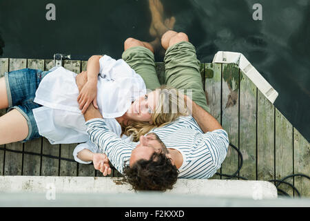 Smiling woman lying on man's lap at the water - Stock Photo