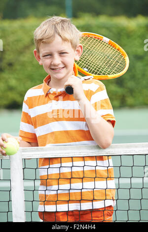 Portrait Of Boy Playing Tennis Standing Next To Net - Stock Photo