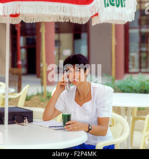 Young businesswoman talking on her cellular telephone on city street - Stock Photo