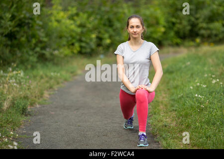 Young sporty girl is warming up outdoors. A healthy lifestyle. - Stock Photo