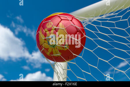 Montenegro flag and soccer ball, football in goal net - Stock Photo