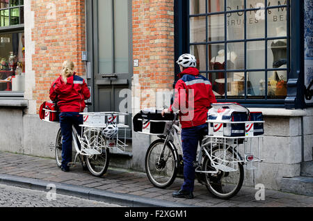 Two post persons on bikes delivering post in Bruges Belgium - Stock Photo