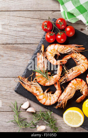 Grilled shrimps on stone plate over wooden table. Top view with copy space - Stock Photo