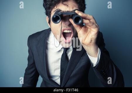 Young businessman is looking through binoculars and is surprised at what he sees - Stock Photo