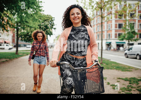 Portrait of happy young woman riding bicycle with another walking in background on city street. - Stock Photo