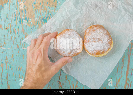 Male hand reaches and picking sweet sugary donut from rustic wooden kitchen table, tasty bakery doughnuts overhead - Stock Photo