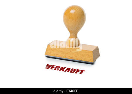 Verkauft (German Sold) printed in red ink with wooden Rubber stamp isolated on white background - Stock Photo