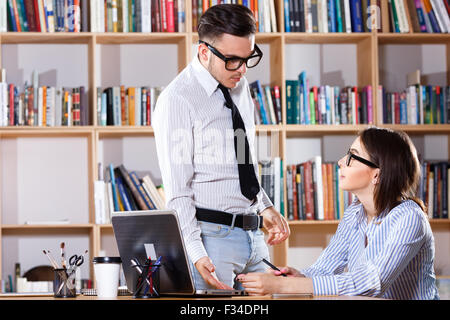 Young confused man, wearing in white shirt, glasses and tie, standing near beautiful woman's table and they are - Stock Photo