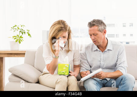 Crying female patient talking to therapist - Stock Photo