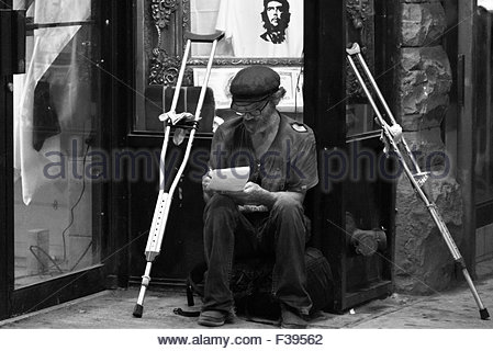 Black and white image of an old man in torn clothes writing on paper with underarm crutches by his side. Disabled - Stock Photo