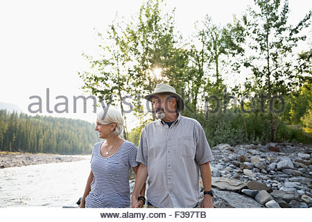 Senior couple walking along riverside - Stock Photo
