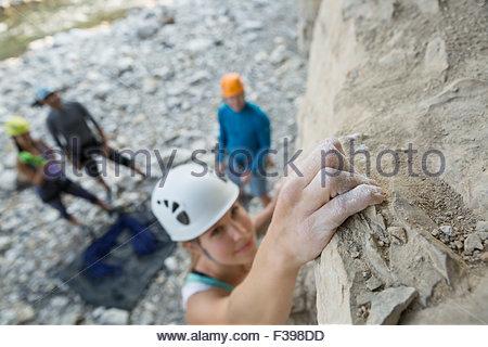 Female rock climber clinging to rock - Stock Photo