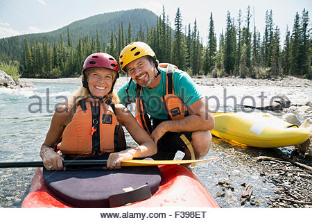 Portrait smiling couple kayaking in river - Stock Photo