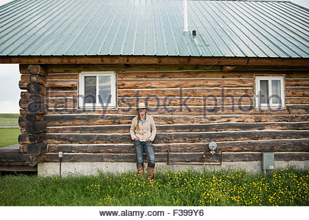 Portrait female rancher standing against cabin wall - Stock Photo