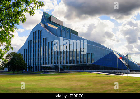 A new modern building of the Latvian National Library with the national flag on a sunny summer day with green lawn - Stock Photo