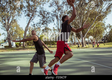 Two young men playing basketball, shooting hoops in the park at sunset - Stock Photo
