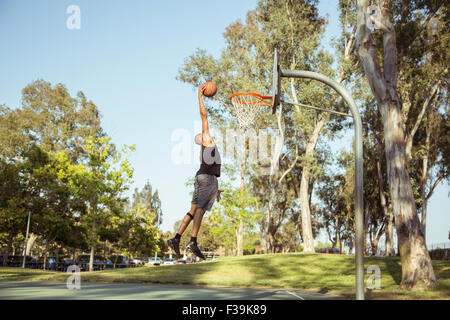 Man shooting basketball  hoops in the park at sunset - Stock Photo