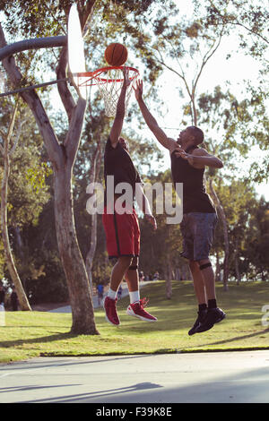 Two young men shooting basketball hoops in the park at sunset - Stock Photo