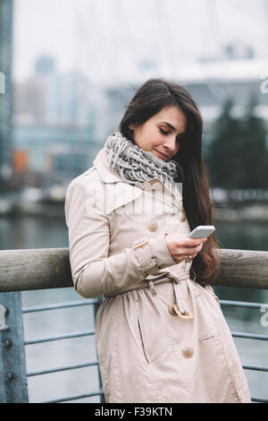 Portrait of a woman standing on a balcony looking at her mobile phone, smiling - Stock Photo