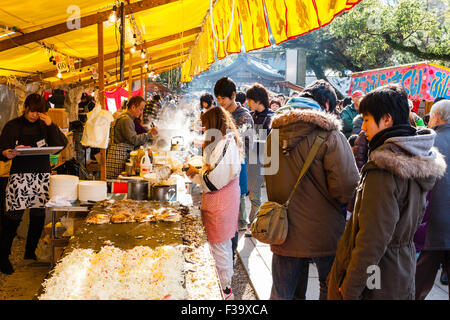 Okonomiyaki stall, outdoors in shrine grounds during the new year festival. View along coutner with okonomiyaki - Stock Photo