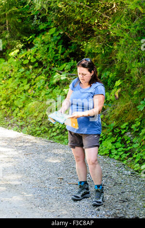 Female hiker examines a map. photographed in Zillertal, Tirol, Austria - Stock Photo