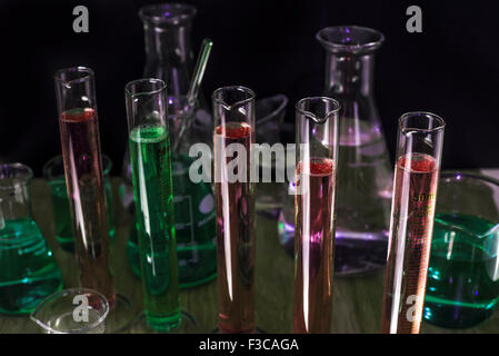 Chemistry test tubes and flasks in a darkened laboratory - Stock Photo