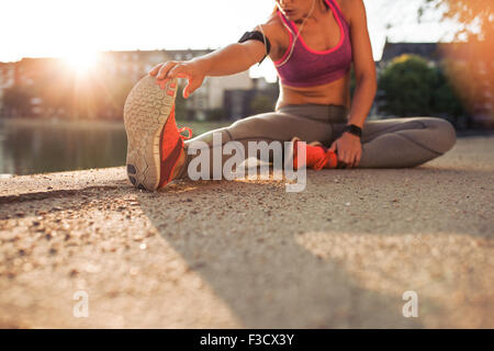 Cropped shot of female runner stretching legs before doing her summer workout. Woman warming up before outdoor workout - Stock Photo