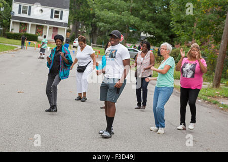 Detroit, Michigan - Members of the Three Mile Block Club dance in a blocked-off street during a neighborhood block - Stock Photo