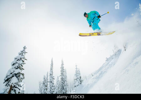 Young man jumping from ski slope - Stock Photo