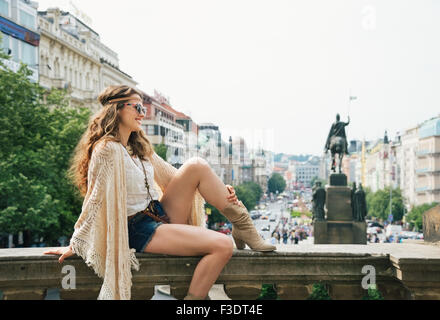 Smiling young trendy hippie woman tourist sitting on stone parapet in the historical center of Prague. In the background - Stock Photo