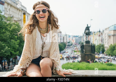 Joyful longhaired hippy-looking woman tourist sitting on stone parapet on Wenceslas Square in Prague. In the background - Stock Photo