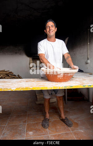 Young baker mixing dough in bowl by hand to be baked in traditional brick oven - Stock Photo